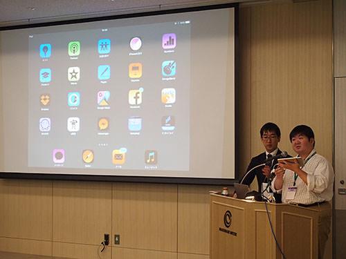 iPadの利用デモを行う伊敷氏(右)と、補佐を行う清家氏(左)